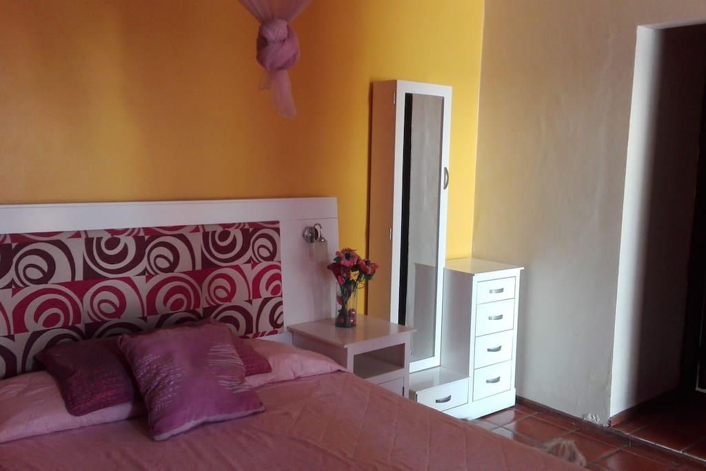La habitación tiene instalado un velo de tul color rosa pálido arriba de la cama, para una mejor protección contra los mosquitos.