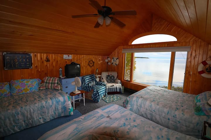 Second floor bedroom with 2 doubles, 1 single, TV, ceiling fan, and lake view