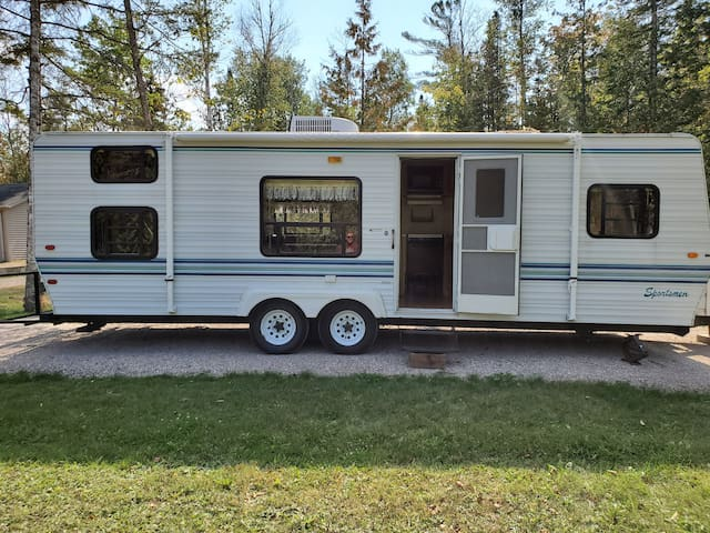 Travel trailer in woods by Crooked River