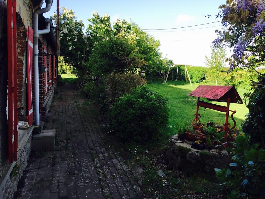 Jardin charmant et spacieux, avec balançoire et bac a sable pour les enfants.