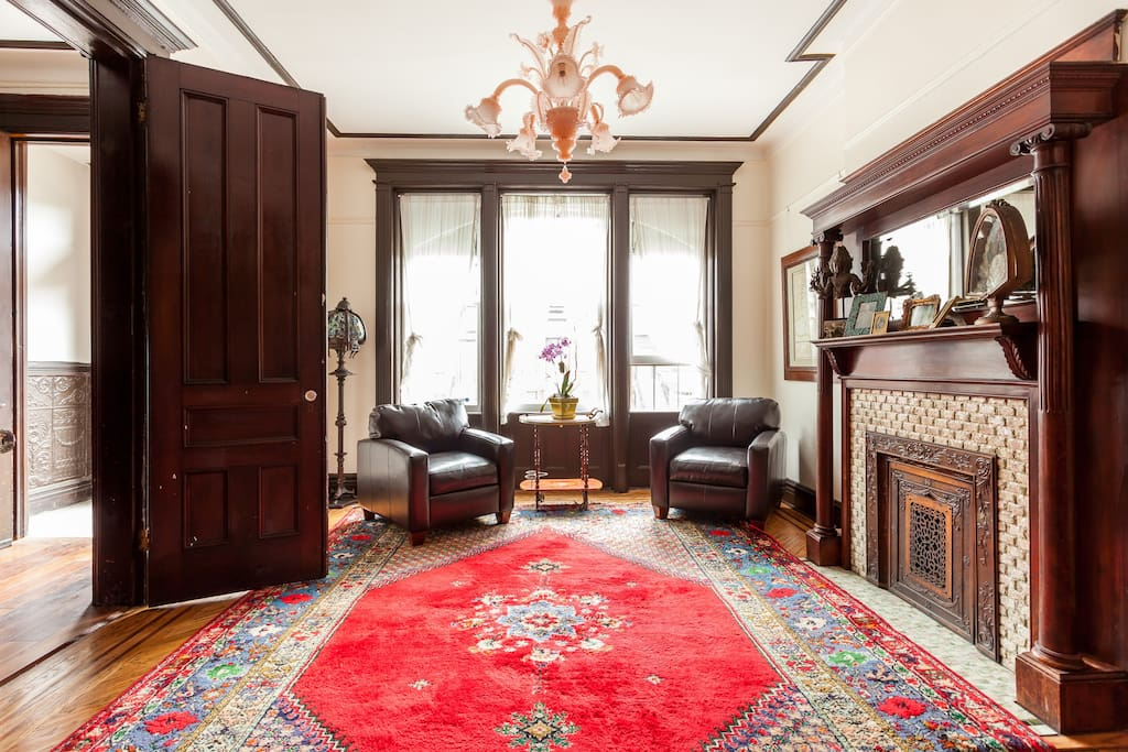 The parlor, adorned with a vintage Italian handblown glass chandelier and plush Moroccan rug.