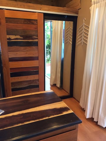 The sliding bathroom door was my design, built locally using local woods only. It's simply magnificent. I know quite a few Guitar builders and this place makes them crazy. When closed, the door exposes a full length mirror with hangers for fdresses to the right. Remember, this is a Tiny House, living small can be liberating. In short, Simple is good.