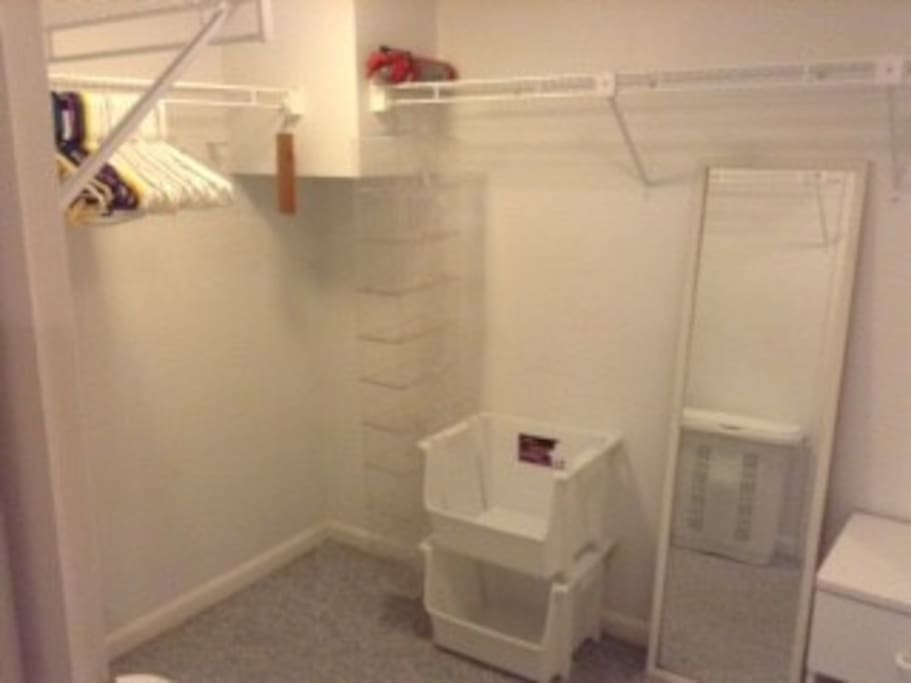 Extra large closet space with room for hanging items, bins for storage and full length mirror.