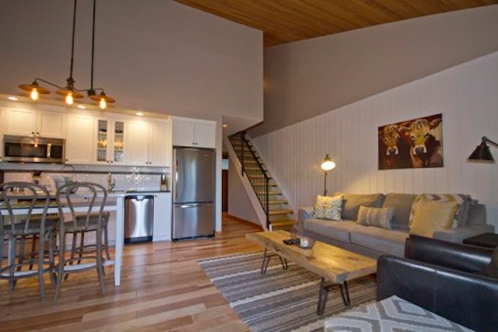 Large living space with vaulted ceilings open to the kitchen, dining for 6.