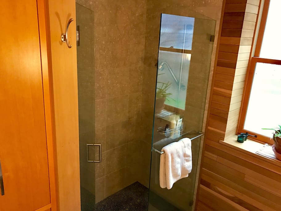 River rock, tile, and double shower heads in this luxurious shower.