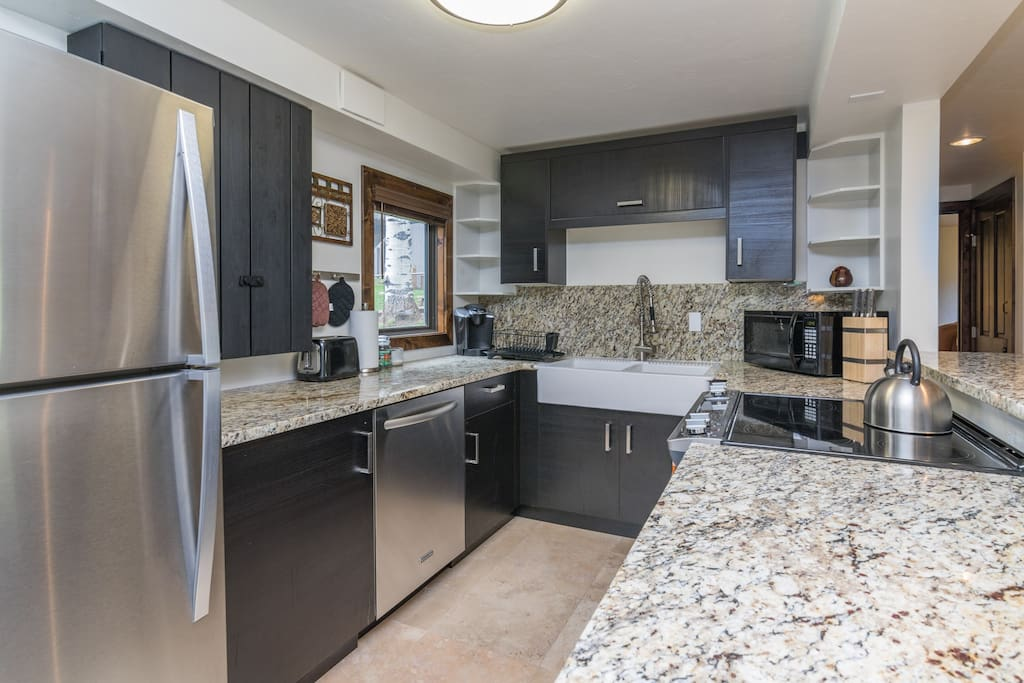 Stainless steel appliances, granite countertops, and updated dark wood cabinetry adorn the kitchen