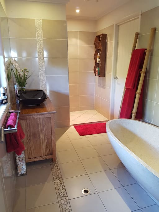 lovelt Balinese bathroom with large walk in shower and stone bath tub