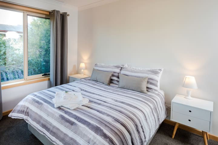 Bedroom three has a small double bed, bedside tables and lamps. Out of sight, this bedroom also has a built-in wardrobe on the right and opposite the bed is a sliding glass door opening onto the back deck.