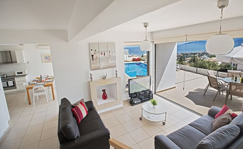 Spacious Living room with widescreen TV, fireplace and doors leading out to the garden