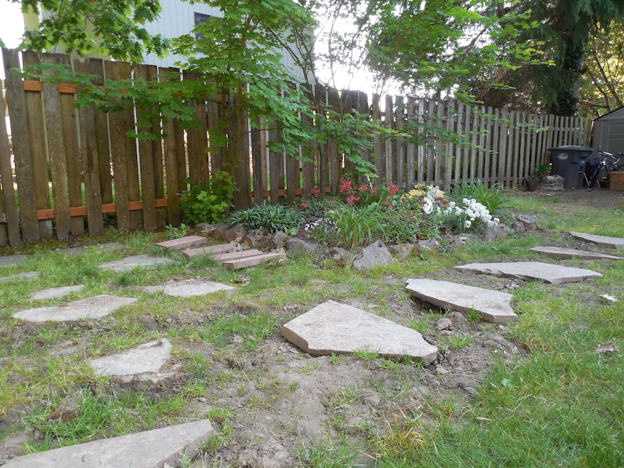 Rocky path and small flower garden in the backyard.