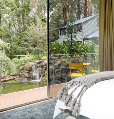 Main bedroom with views toward the waterfalls and natural pool and down toward the Yarra Valley