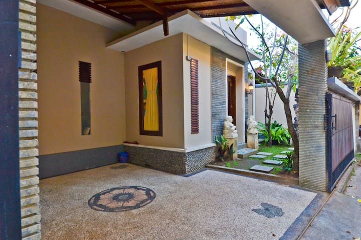 Front entrance with car port and small garden.