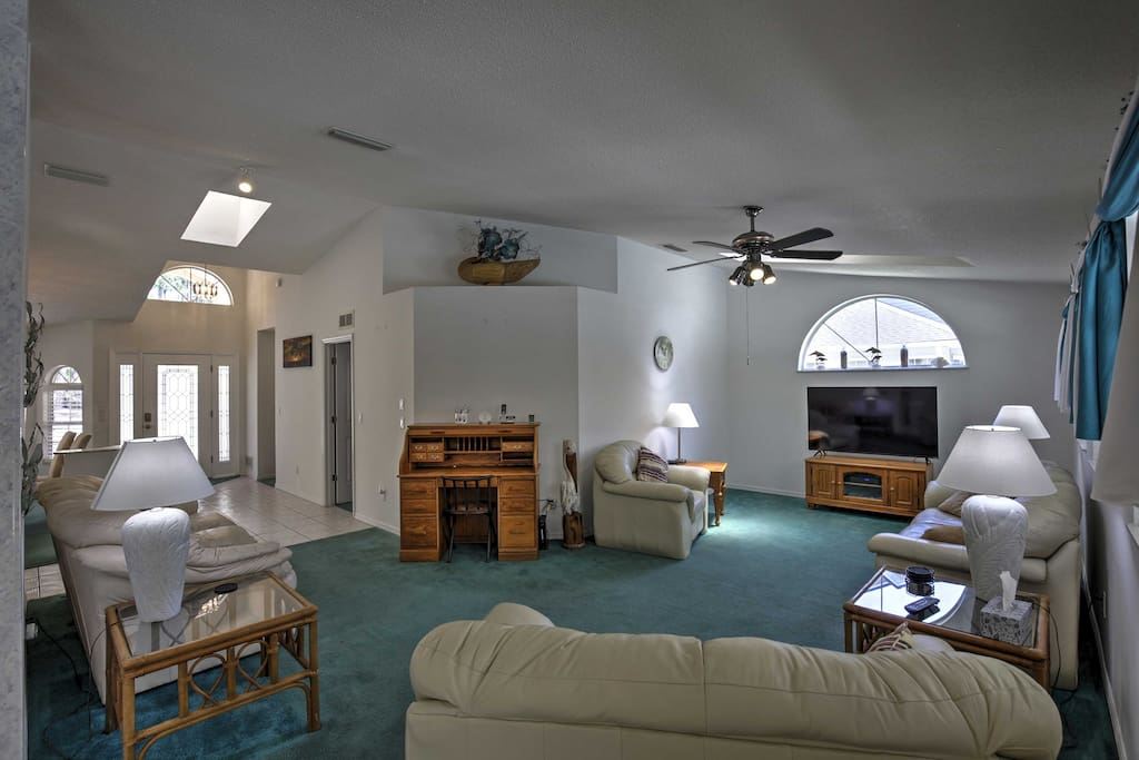 The open living room has 3 couches and an arm chair, perfect for watching your favorite shows on the flat-screen cable TV after a long day in the sun.