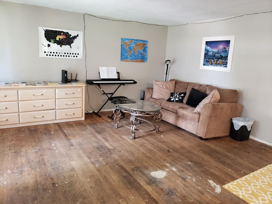 Main floor living room. You can see the floor has some paint stains.  It is old hardwood that needs refurbishing or covering up. We prioritized a central Air conditioner and just had one installed. We will save up for a floor next!