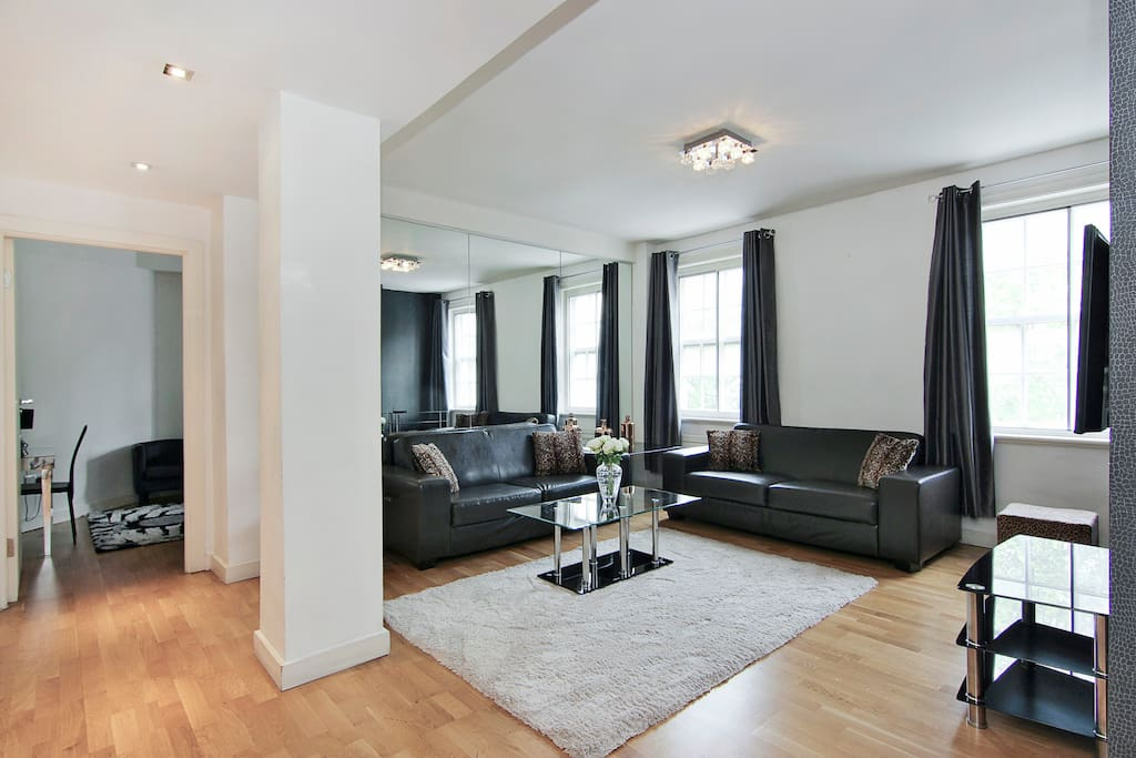 Bright, spacious lounge with 2 large leather sofas and dining table and chairs.