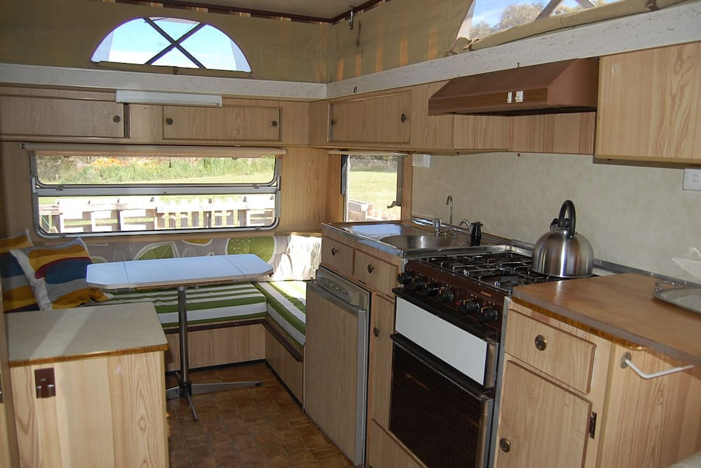 Dinette, kitchen with 4 burner stove, grill, oven and fridge.