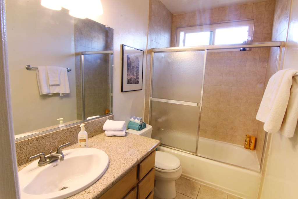 Clean and fresh bathroom with granite counters and tile floors