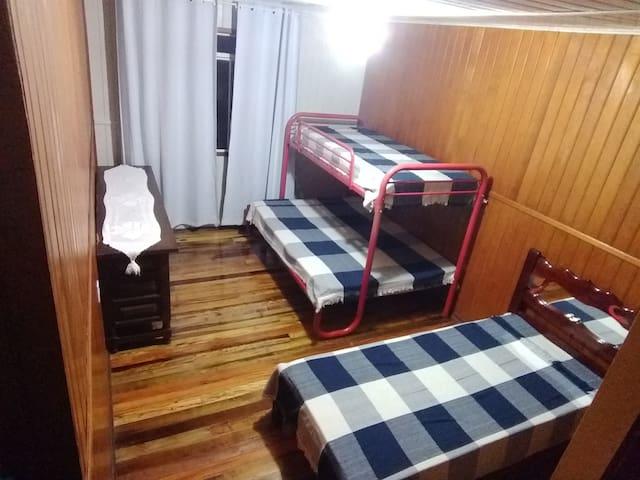 Quarto três: Possui um beliche, sendo casal em baixo e solteiro em cima. Ainda temos mais uma cama de solteiro, um armário grande e uma cômoda.