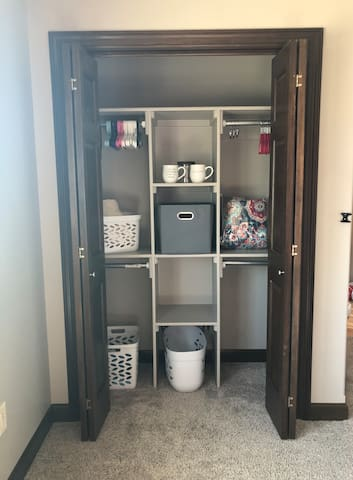 Closet with cubbies and hangers, trash can and laundry basket