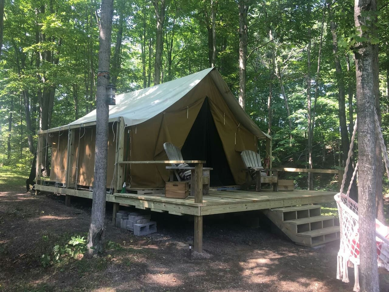 This is a 16 x 16 foot tent outfitted with a comfortable, well dressed queen size bed tucked just inside the woods with the front porch facing the pond.