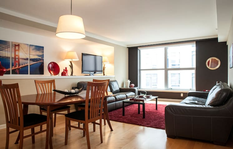 Here is a view of your living room. You have a large dining area, two leather couches, flat screen TV, and huge windows.