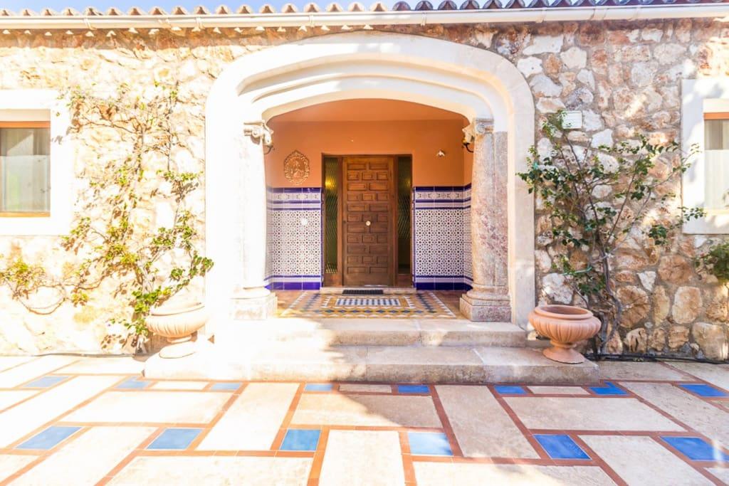 Vista de la entrada de la casa, diseñada con el estilo y carácter típico andaluz. Los escalones conducen a la entrada con una exuberante buganvilla.