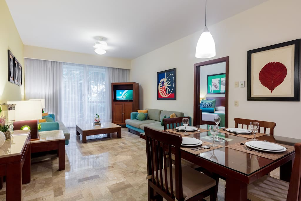 Open concept gathering space features a dining area for 4 and flat screen TV.