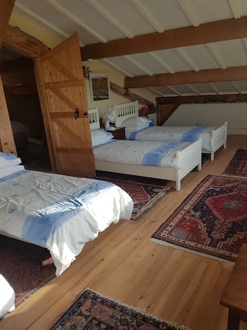 Bedroom 5 , with 4 single beds, side tables, Fans, persian rugs , smoke alarm and panoramic view of the patchwork farms and woods. No Air conditioning.