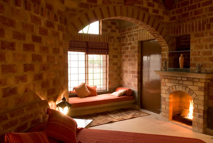 Bedroom with a fireplace and a settee