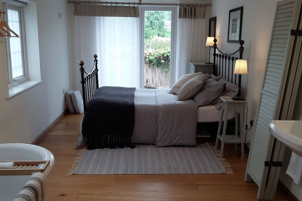 The bedroom leading out on to the patio. Muslin curtains can be drawn for privacy.