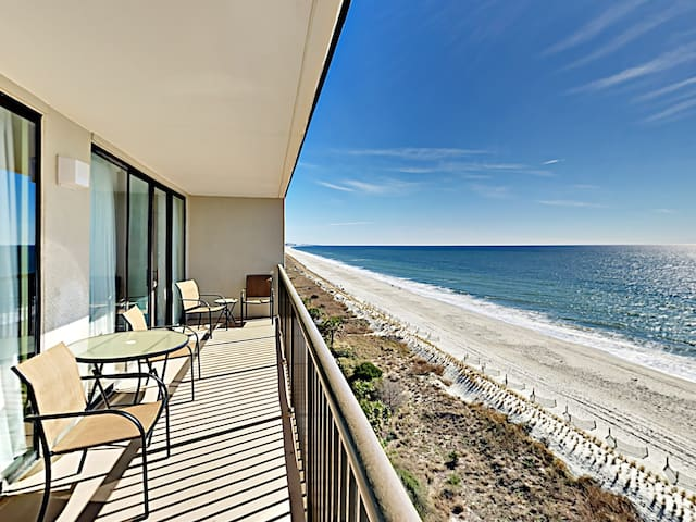 A private balcony with seating for 4 overlooks the ocean.