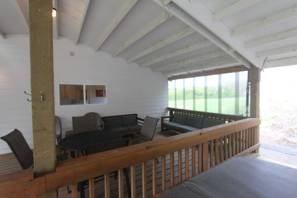 Covered patio with lots of seating and BBQ