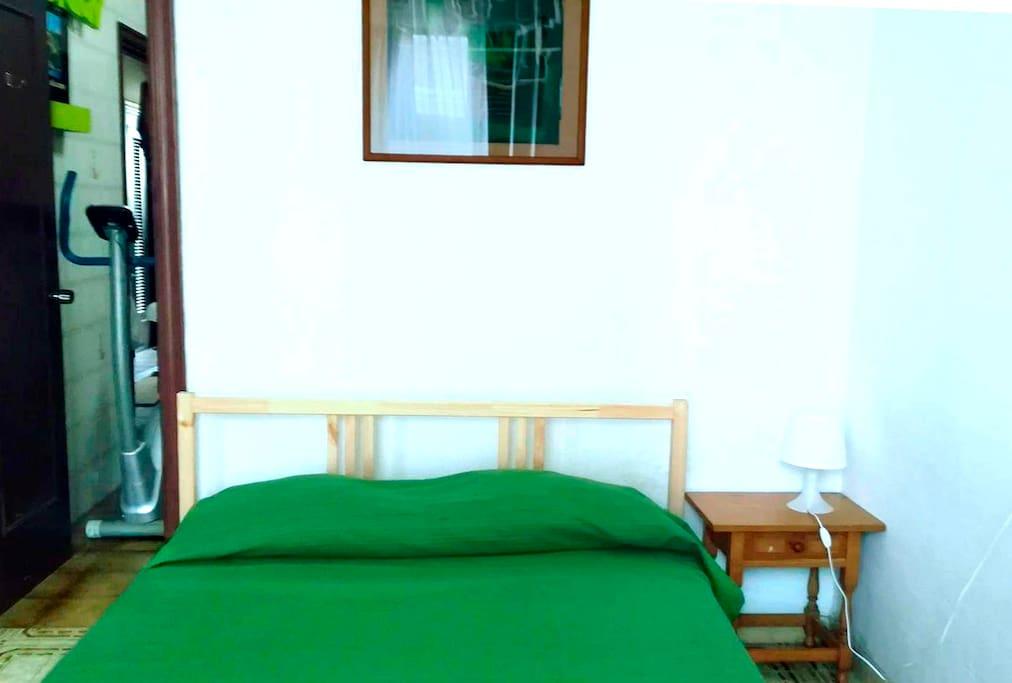 La habitacion ,la cama,mesita de noche y lampara,da acceso al baño privado.