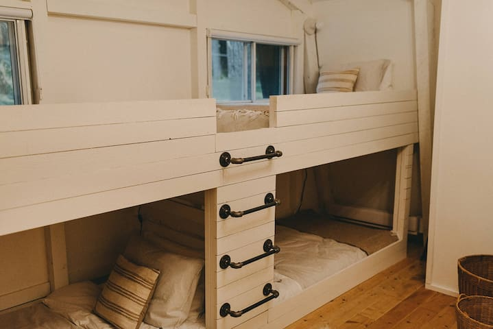 Bunkroom with four single beds each with individual lamps