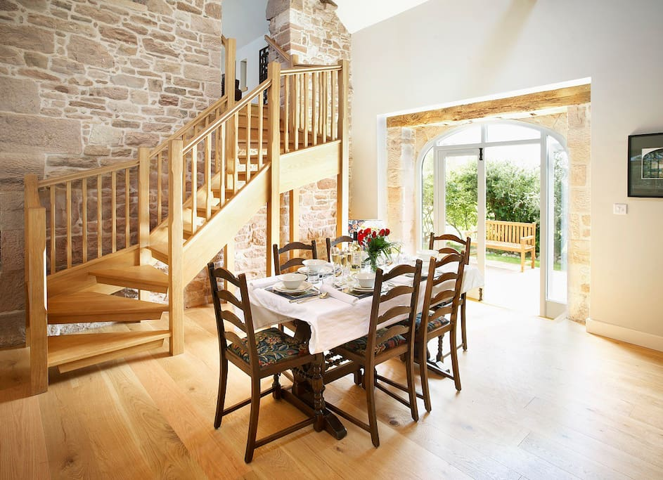 The kitchen table at Wythburn with the doors open onto a second sandstone terrace.