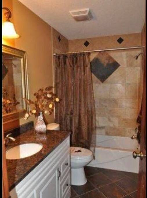 Main bathroom upstairs, granite counter top, single sink, shower/bath. (Please note, decor may be different during your stay)