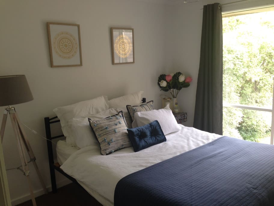 The bedroom with queen bed, bedside table and lamp.