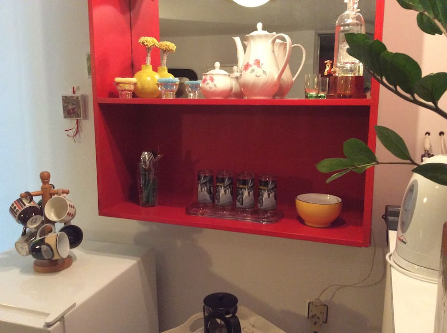 The bar is equipped with appliances and utilities such as espresso and black coffee maker, a water kettle, a toaster, a juicer, cups, glasses of water, coffee, sugar, tea with local herbs.