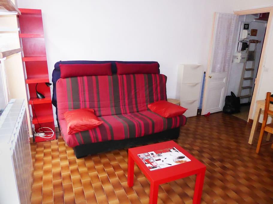 Salle principale avec le canapé et le matelas double derrière.