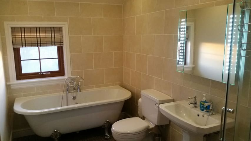 Roll top bath with shower to the right of photo.
