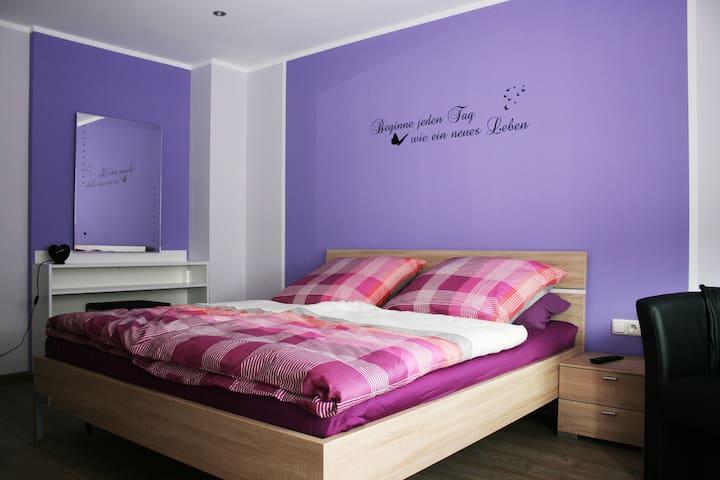 Modernes Schlafzimmer mit Doppelbett,Schminktisch und großen Flachbildfernseher.