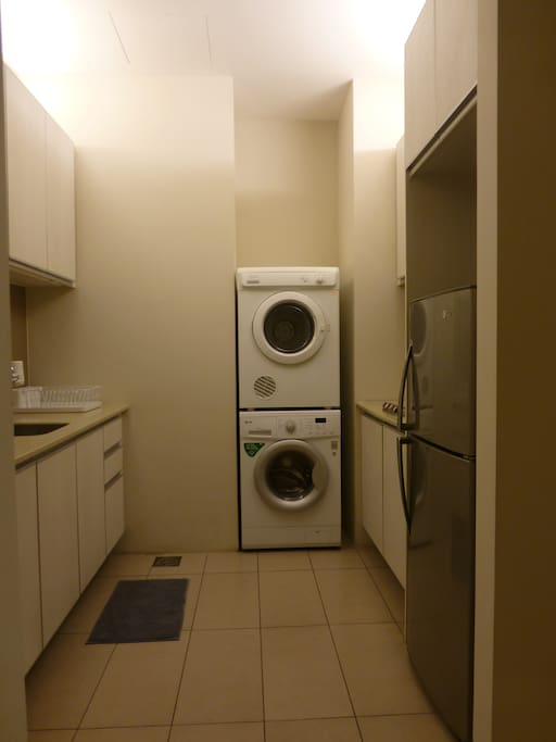 Kitchen, including a sink, a microwave oven, a kettle, an electric stove, a 2-door fridge, washer & dryer