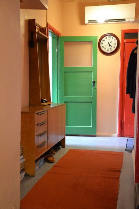The hall view from the room. Green door to the Kitchen, bathroom and garden, red to the toilet.