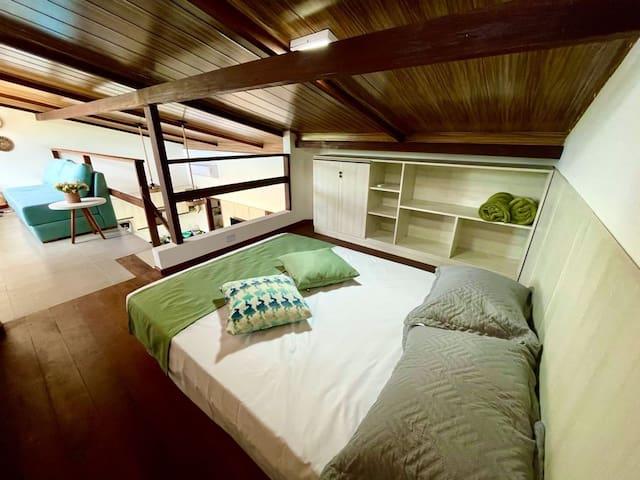 Quarto do mezanino com uma cama baixa estilo japonesa de casal, cômoda e ar Split 12000 Btus