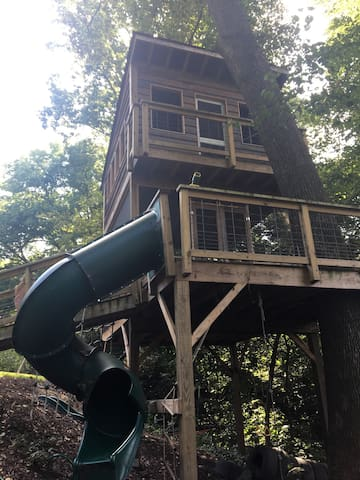 Here's a view of the full treehouse from the ground. Under the treehouse, you'll find a trapeze, climbing rope, disc swing, and other fun playground equipment for children.