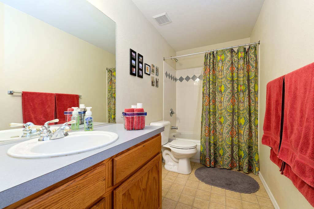 A spacious private bath with tub/shower, sink, vanity, and stocked with towels, shampoo, soap, hairdryer, and toothpaste.
