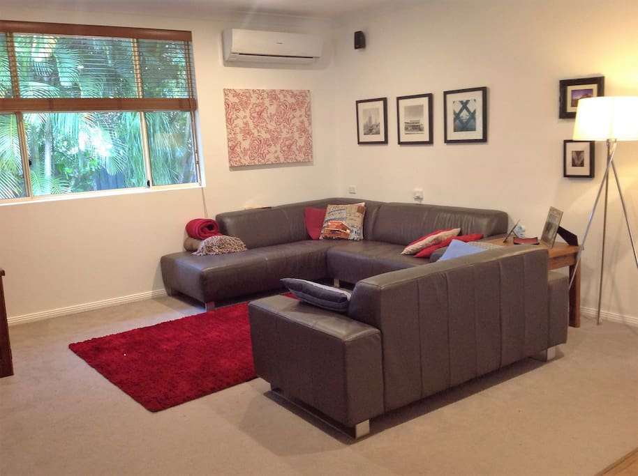Open plan living room with TV, aircon and fire