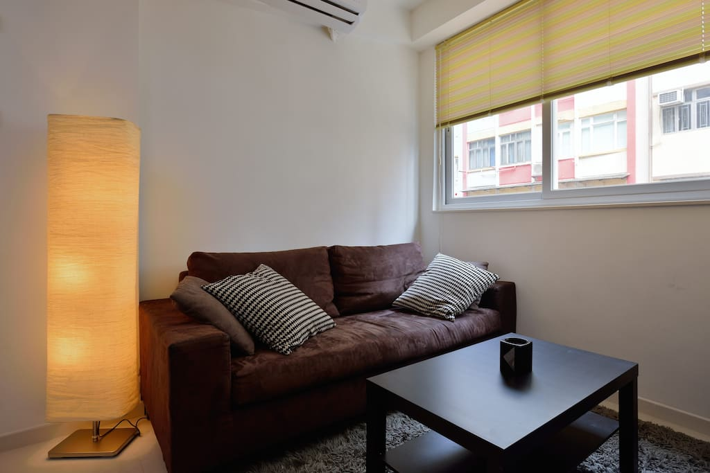 bright living room with sofa bed for one person and air con