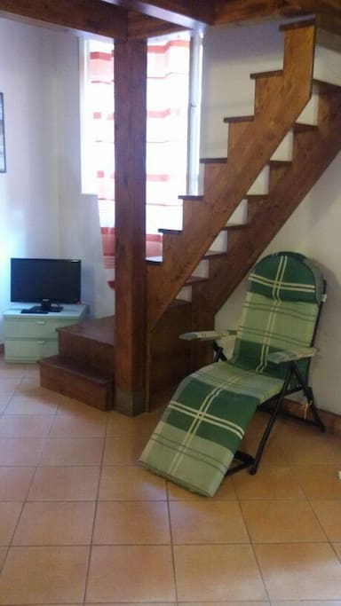 ingresso con divano sedia sdraio e televisione