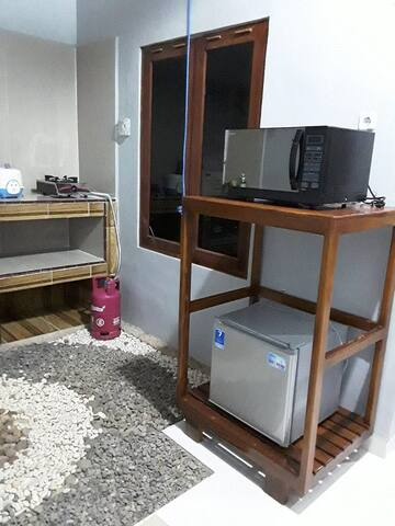 Kulkas (50L) dan microwave (25L) di dapur.  The refrigerator (50L) and the microwave (25L) in kitchen.